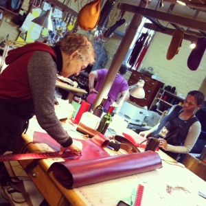 Sarah uses a square as an edge to pattern the leather.