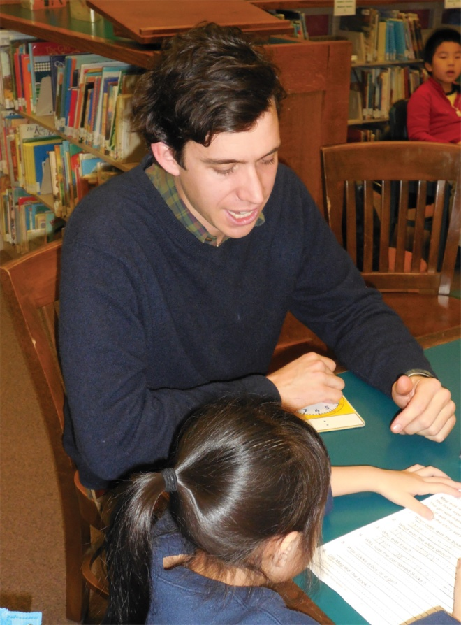Joseph working with a student at the McKinley Branch Library.